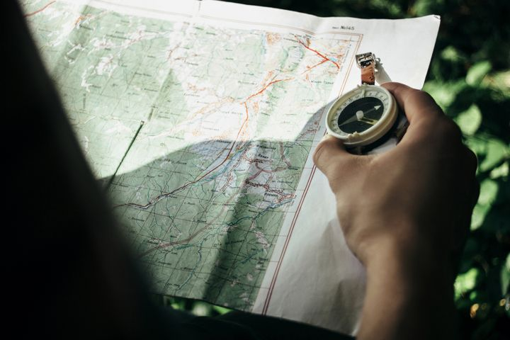 Traveler Exploring Map With hiking Compass