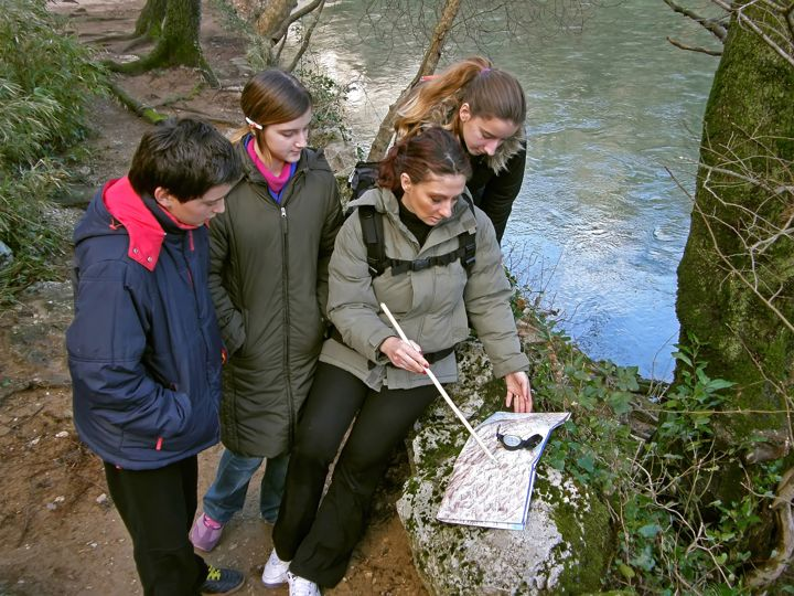 group orienteering in nature with hiking compass and map