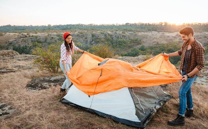 happy young couple setting tent outdoors